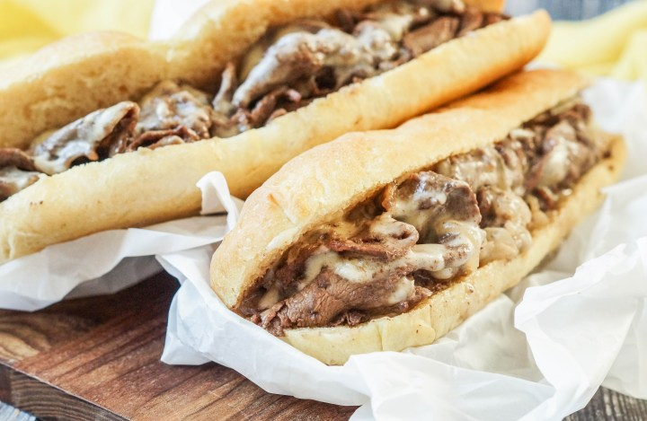 Two Philly Cheesesteak on a sheet of white parchment.