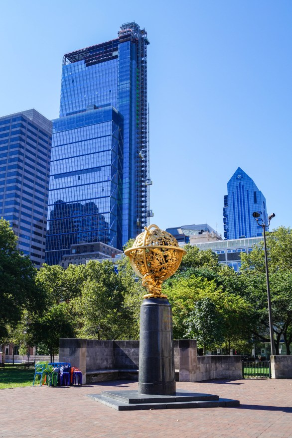 Gold round statue outside The Franklin Institute with tall blue buildings in the background.