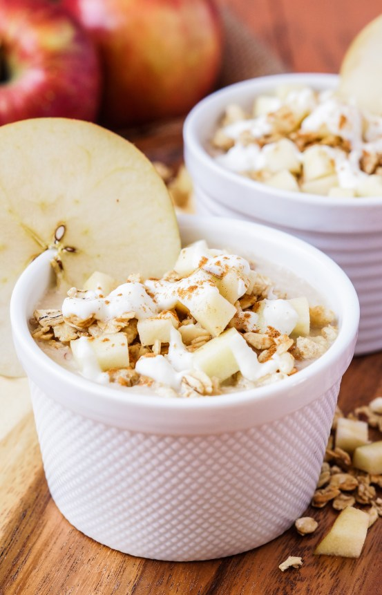 Side view of Apple Pie Smoothie Bowl in two white ramekins and topped with apple, granola, yogurt, and ground cinnamon.