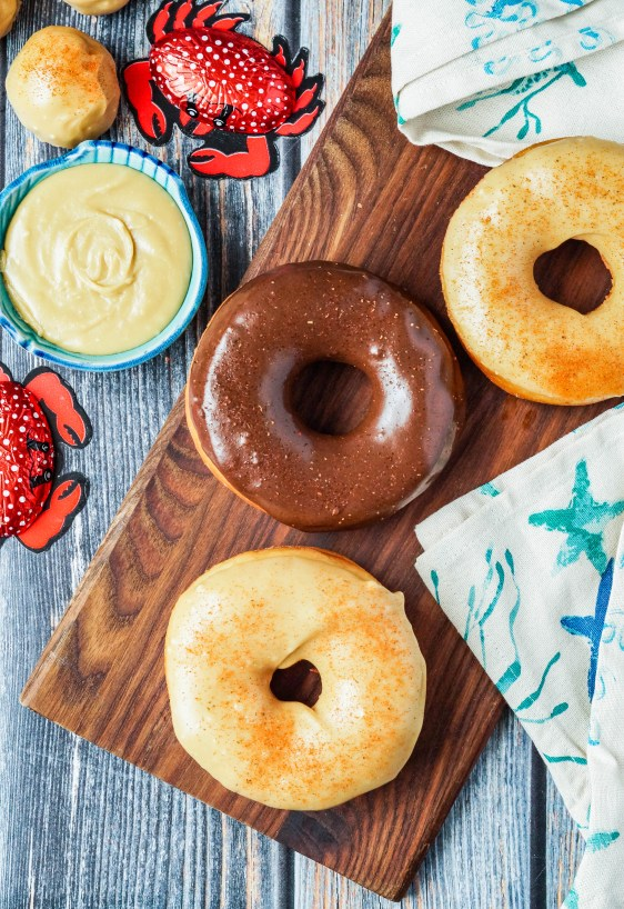 Aerial view of three Old Bay Doughnuts on a wooden board next to chocolate crabs, a tan towel with blue starfish, and a bowl of caramel glaze.