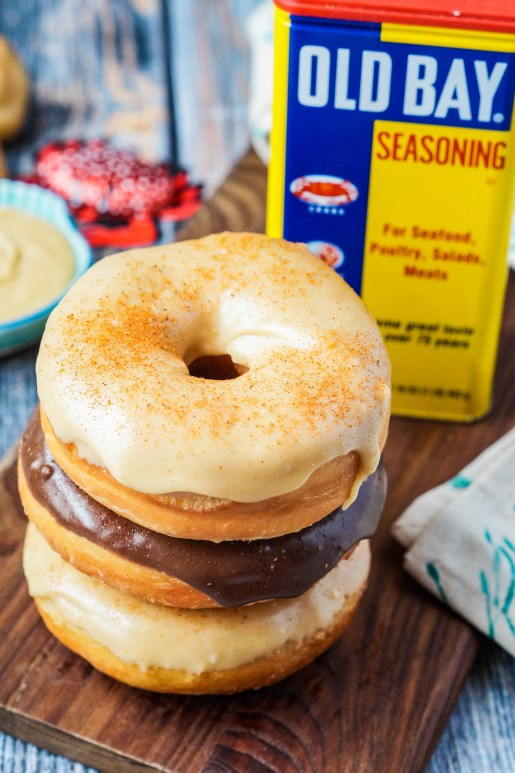 Three Old Bay Doughnuts stacked on a wooden board in front of a container of Old Bay Seasoning.
