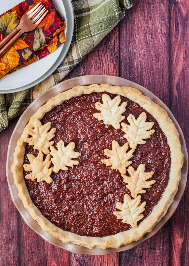 Sweet Potato Pie in a tan ceramic pie dish with leaf pie crusts decorating the top.