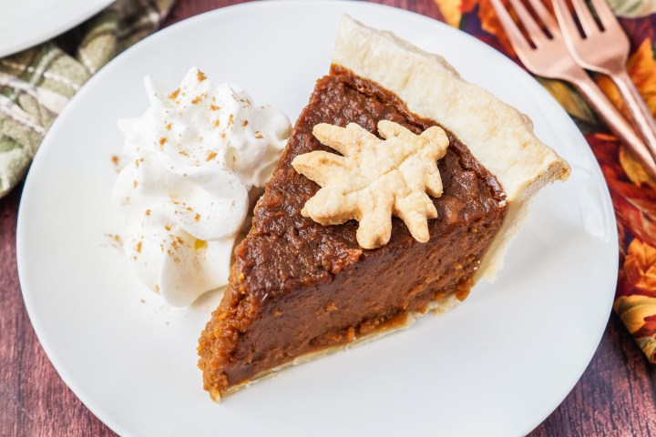 A slice of Sweet Potato Pie on a white plate with whipped cream.