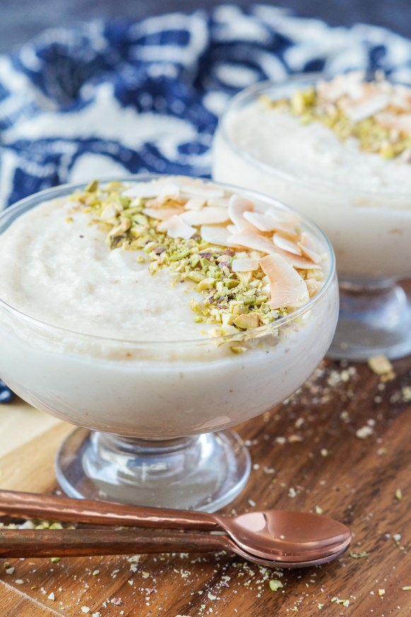 Side view of Keskul-e-Fugara (Turkish Milk and Almond Pudding) in two glasses with two copper spoons in front.