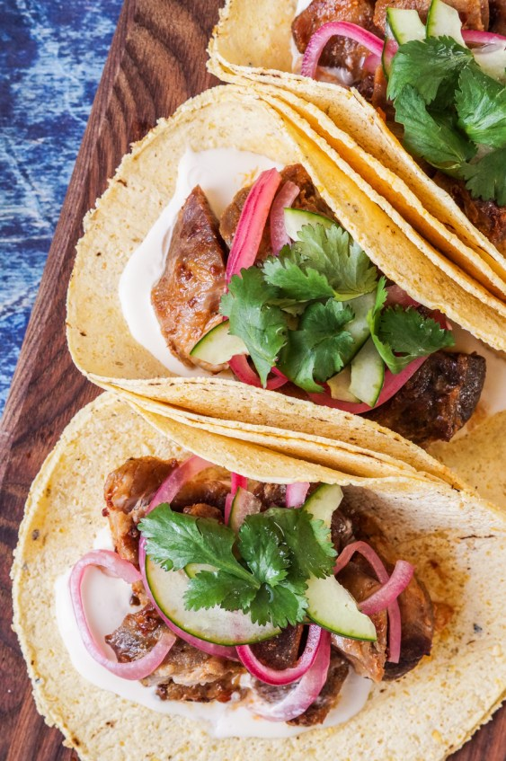 Close up of three Carnitas Tacos topped with cilantro and pickled onions.