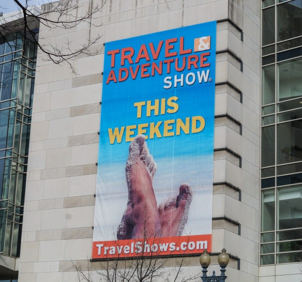 Sign on side of building: Travel & Adventure Show This Weekend- travel shows . com