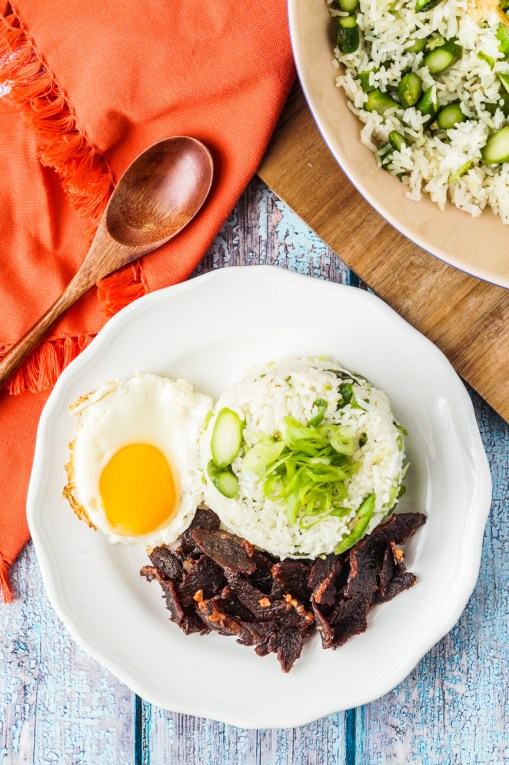 Aerial view of Asparagus Fried Rice on a white plate with beef and a fried egg.