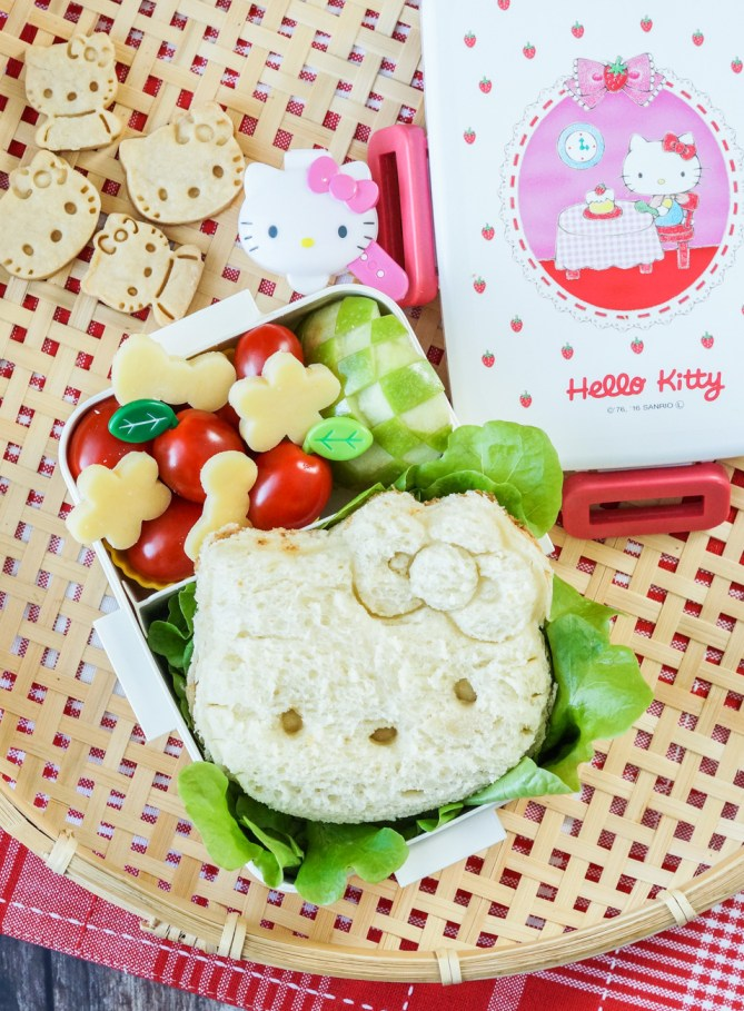 Aerial view of Hello Kitty Bento with sandwich, lettuce, cherry tomatoes, cheese, and Hello Kitty cookies.