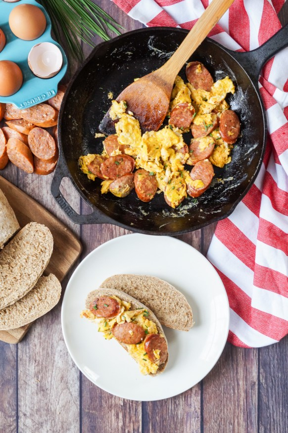 Jajecznica (Scrambled Eggs with Polish Sausage) over bread slices on a white plate with more in a cast iron skillet next to eggs in a blue dish, sausage slices, bread slices, chives, and a red and white striped towel.