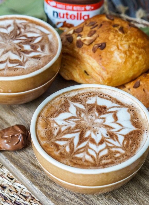 Nutella Latte in two brown mugs with a jar of Nutella and two croissants in the background.