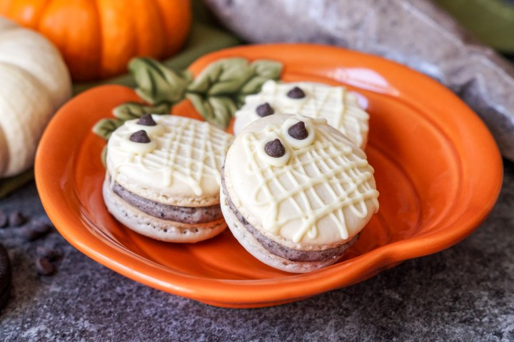 White Mummy Macarons with a cookies and cream center on an orange pumpkin plate