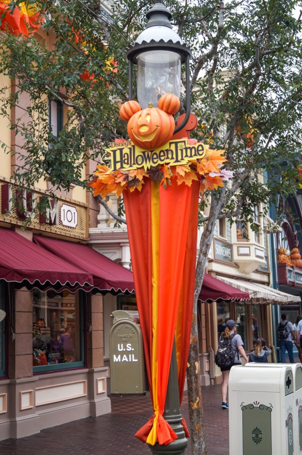 Disney's Halloween Time sign with Mickey Mouse pumpkin on lamp post