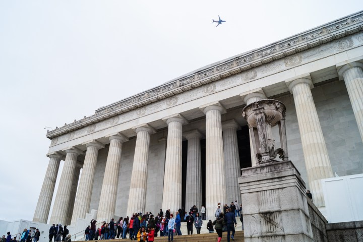 People standing on stairs in front of Lincoln Memorial with a plane flying above
