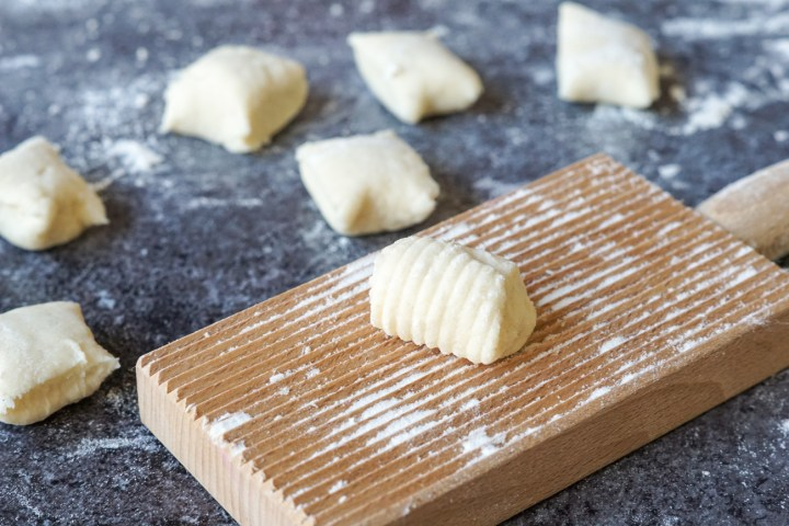 Forming the Burrata Gnocchi on a wooden gnocchi board with ridges with 6 more cut gnocchi in the background.