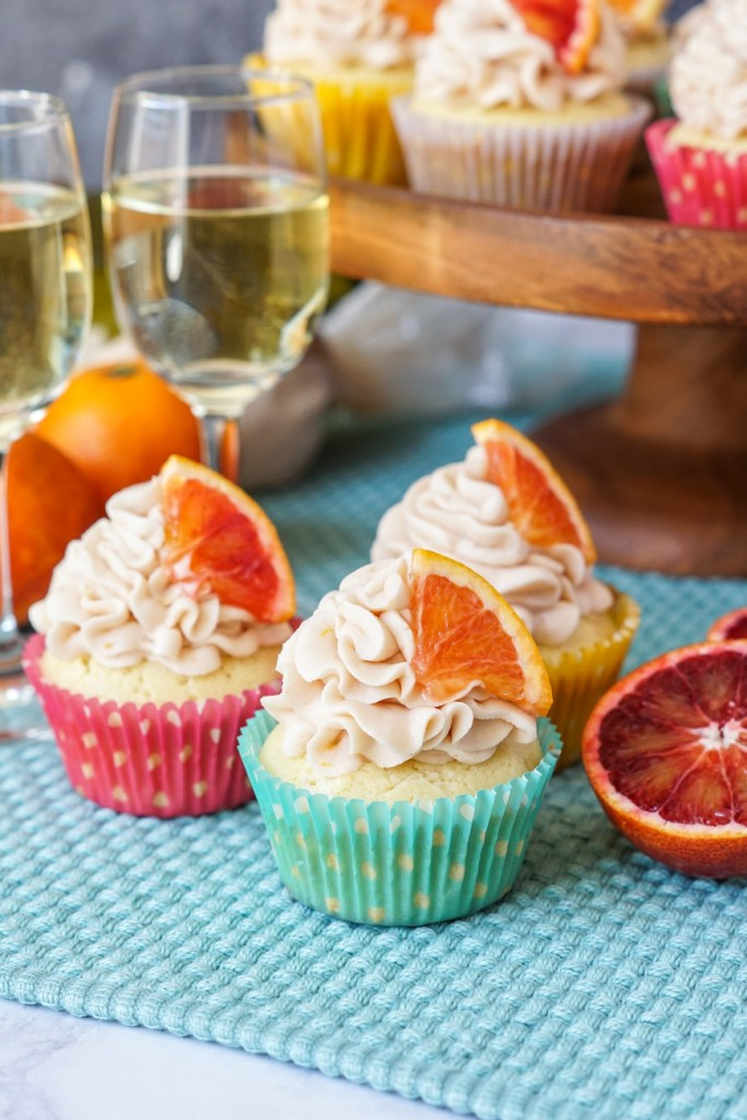 Blood Orange Chardonnay Cupcakes in front of two glasses of white wine with more cupcakes in the background.