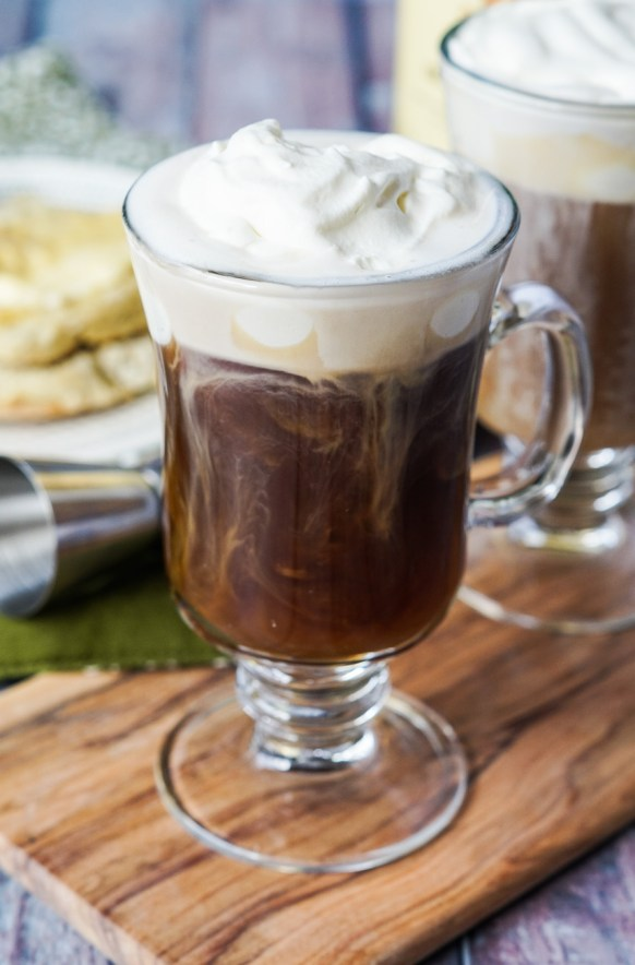 Close up of Irish Coffee in a tall glass mug on a wooden board.