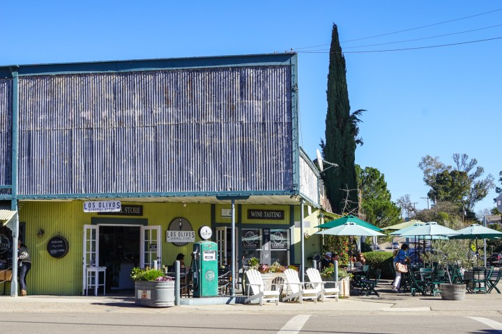 Outside Los Olivos General Store with tables, chairs, reclining chairs, and a retro gas pump