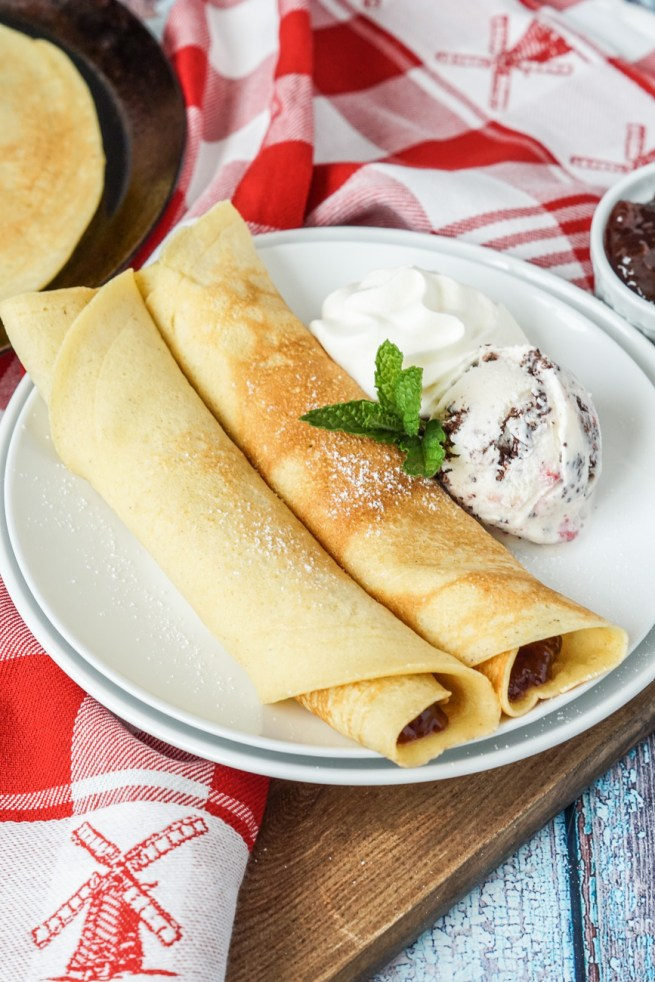 Close up of Pandekager (Danish Pancakes) with strawberry jam and ice cream.