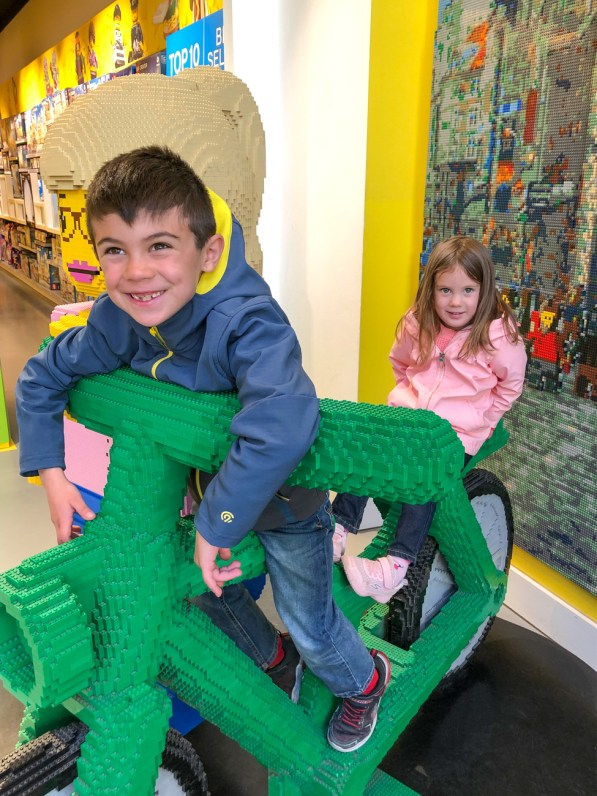 Sitting on the Lego bike at the Lego store