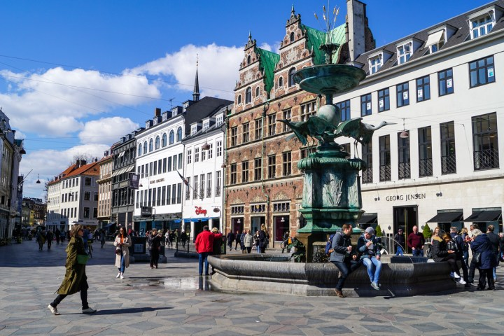 People walking next to the buildings and fountain in Strøget