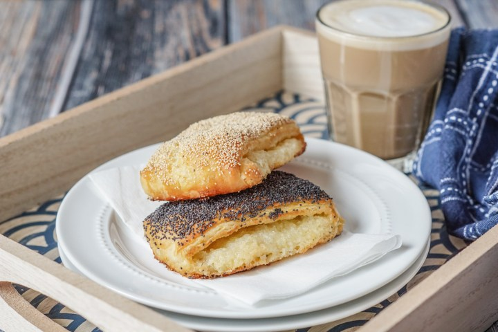 Tebirkes (Danish Poppyseed Pastries) on a white plate with coffee