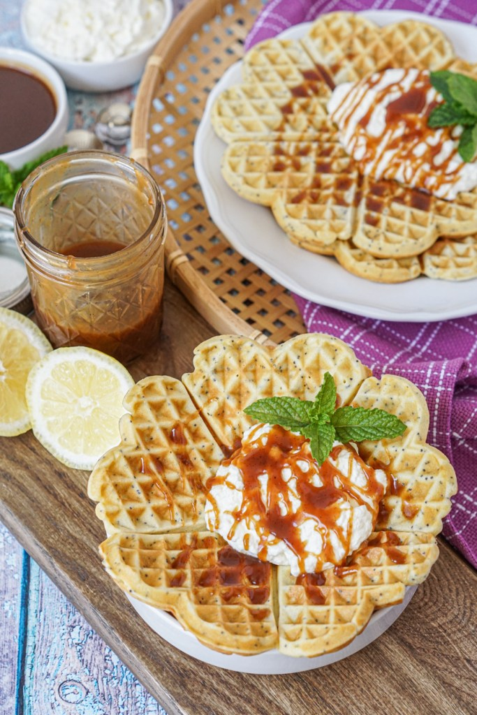 Birkesvafler (Poppy Seed Waffles) with caramel sauce, whipped cream, and fresh mint leaves