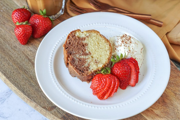 Ciambella Del Mattino (Morning Bundt Cake) on a plate with whipped cream and strawberries