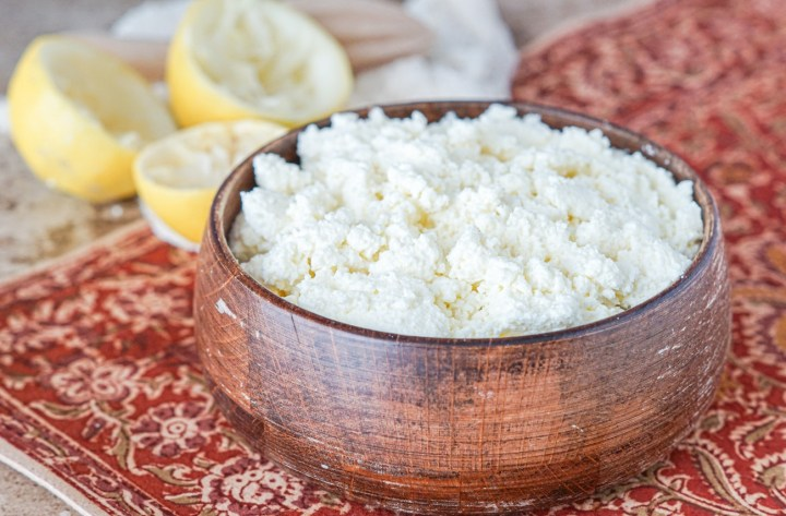 Ayib (Homemade Fresh Cheese) in a wooden bowl with lemon slices and a cheesecloth in the background.