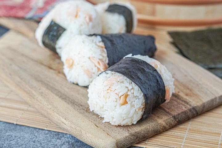 A variety of four Sake Onigiri (Salmon Rice Balls) on a wooden board.