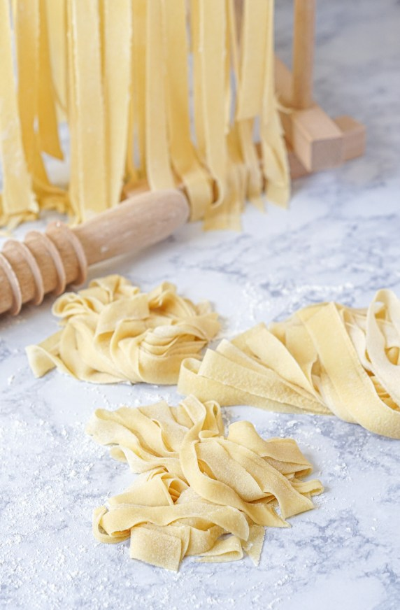 Fresh pappardelle for Pappardelle con Ragu di Funghi Misti (Pappardelle with Mixed Mushroom Ragù) arranged in three nests next to a wooden cutter and more hanging in the background.