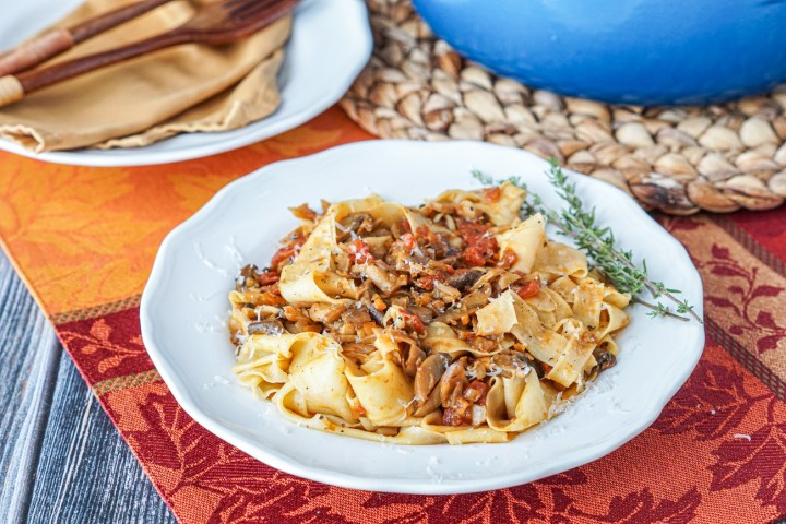Pappardelle con Ragu di Funghi Misti (Pappardelle with Mixed Mushroom Ragù) on a white plate with two sprigs of thyme.