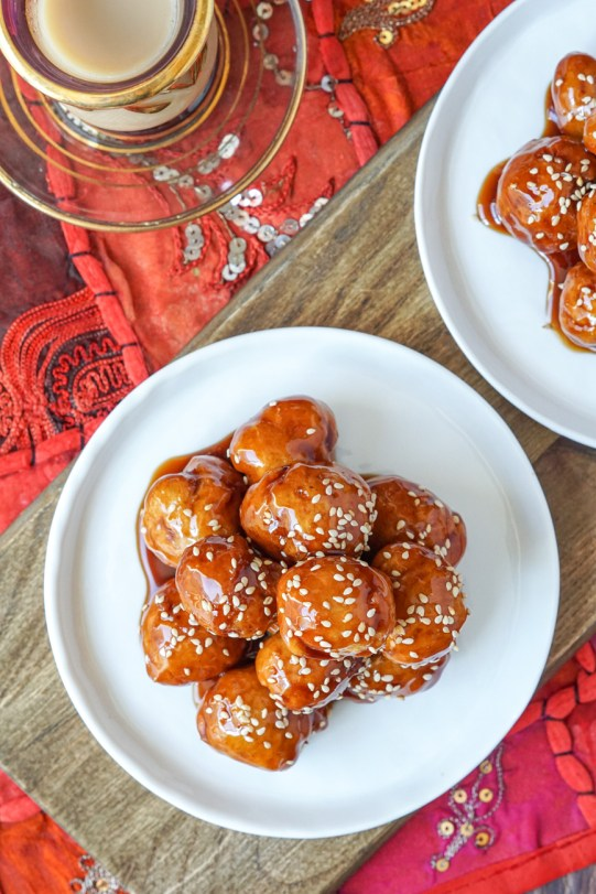 Luqamaat (Fried Dumplings with Date Syrup) topped with sesame seeds