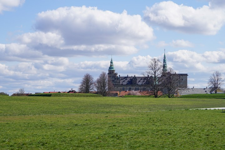 View of Kronborg Slot in the distance with a large green field.