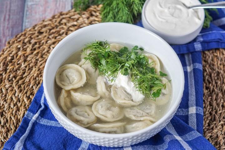 Siberian Pelmeni Dumplings in a broth with fresh herbs