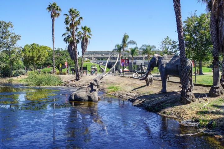 Tar pit at the entrance of the La Brea Tar Pits. Statue of elephant stuck in the tar