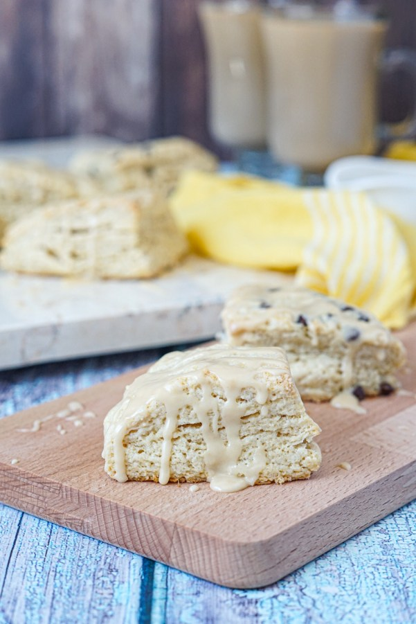 Irish Cream Scones on a wooden board with two glasses of coffee in the background.