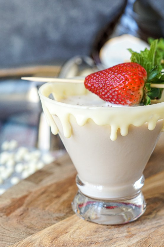 White Chocolate Espresso Martini with a white chocolate ganache rim and topped with a strawberry on a pick.