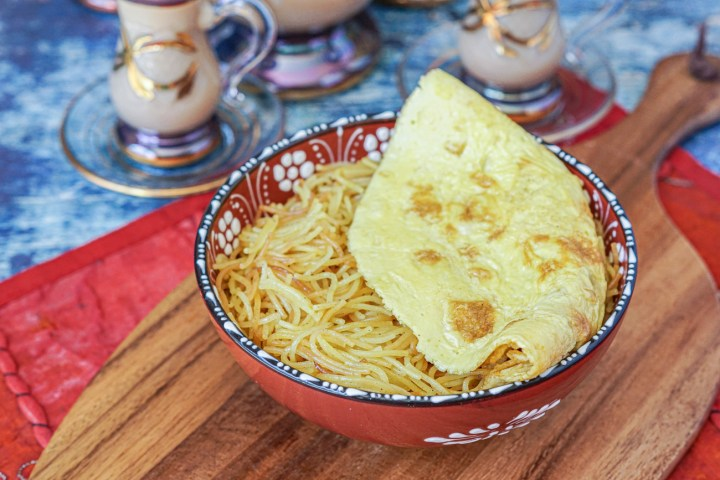 Balaleet (Emirati Sweet Vermicelli and Egg Omelet) in a red clay bowl with white flowers on a wooden platter.