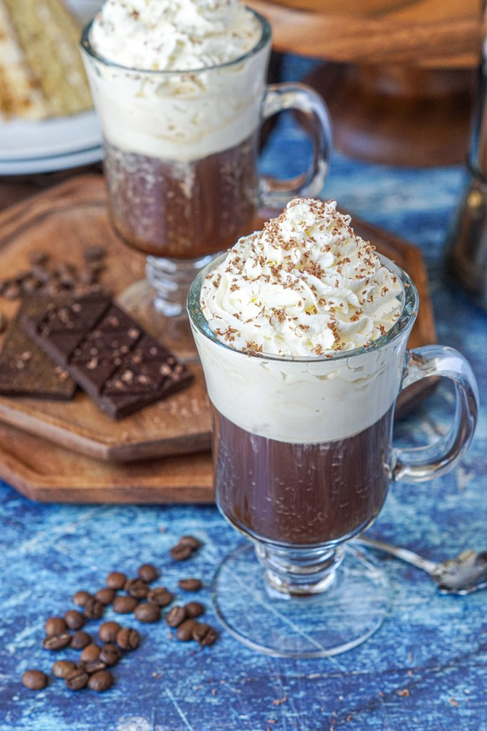 Einspänner (Viennese Coffee with Whipped Cream) in a tall glass with chocolate shavings over the top.