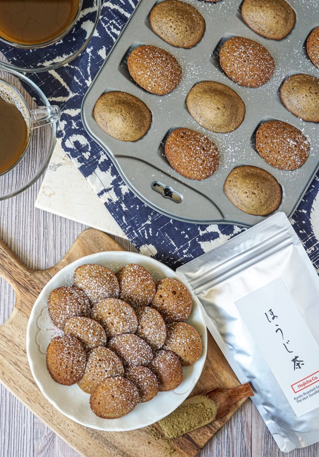 Aerial view of Hojicha Madeleines with a few on a white plate and more in a Madeleine pan next to a bag of hojicha powder and two cups of hojicha tea.