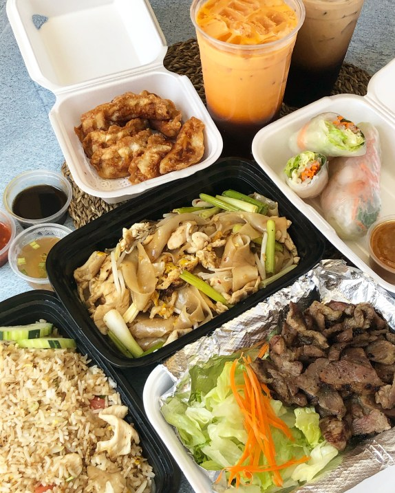 Takeout from Suki Time Thai Kitchen- BBQ Pork with Tiger Sauce, Chicken Fried Rice, Kua Gai (stir-fried flat rice noodles with egg, chicken, carrots, green onions, and bean sprouts), Summer Roll, Fried Dumplings (with ground chicken and mixed vegetables), and Thai Ice Coffee.