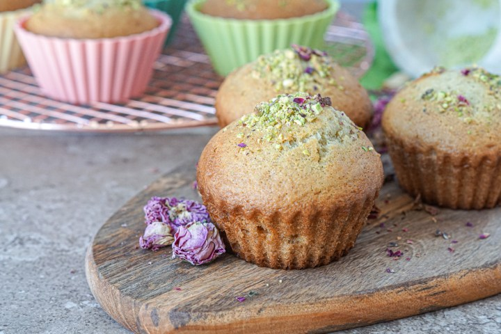 Three Yazdi Cupcakes on a wooden board topped with ground pistachios and rose petals with more cupcakes in the background on a round copper wire rack.