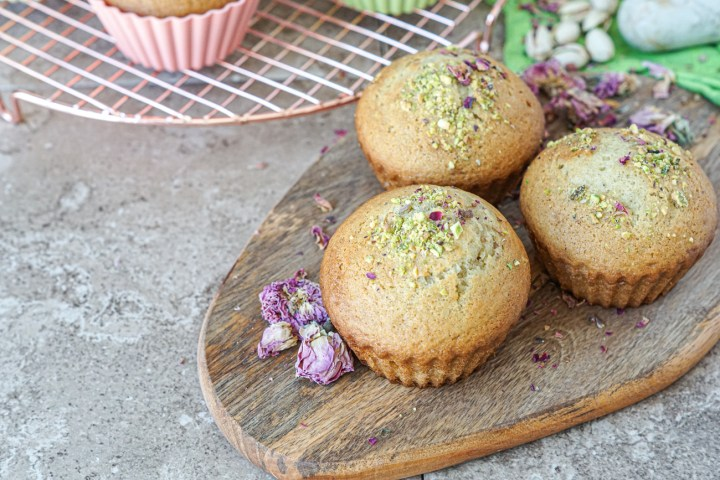 Three Yazdi Cupcakes on a wooden board with dried rose petals.