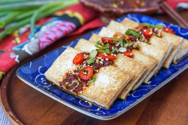 Seven pieces of Dubu Buchim (Panfried Tofu with Soy Chili Sauce) on a blue rectangular plate on a wooden platter. It is next to a red floral towel, green onions, and the soy chili sauce in a leaf shaped bowl in the background.