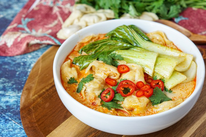 Red Curry Chicken Wonton Soup in a white bowl topped with Bok Choy, cilantro, and sliced red chilies with wontons and cilantro in the background.