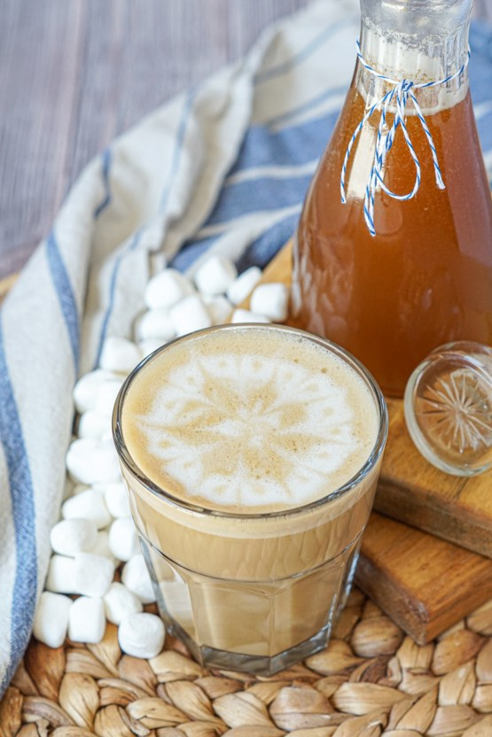 Latte in a glass cup with a flower design on top next to a glass jar of Toasted Marshmallow Syrup, miniature marshmallows and a blue/white striped towel.