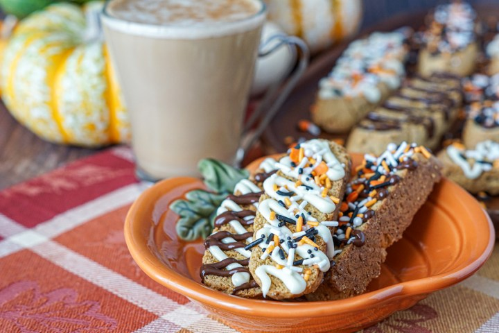 Three Pumpkin Spice Biscotti on a pumpkin plate next to a latte in a clear glass and more biscotti on a wooden board. There are white/orange pumpkins in the background.