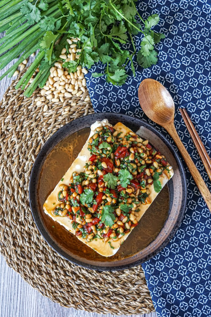 Aerial view of Silken Tofu with Pine Nuts and Pickled Chiles on a brown plate next to a wooden spoon, chopsticks, green onions, pine nuts, and cilantro.