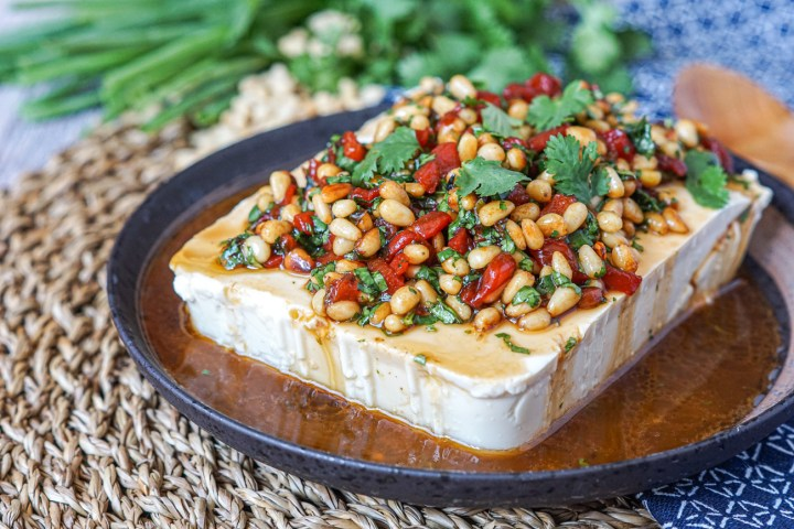 Silken Tofu with Pine Nuts and Pickled Chiles on a dark brown plate next to green onions, pine nuts, cilantro, a blue towel, and a wooden spoon.