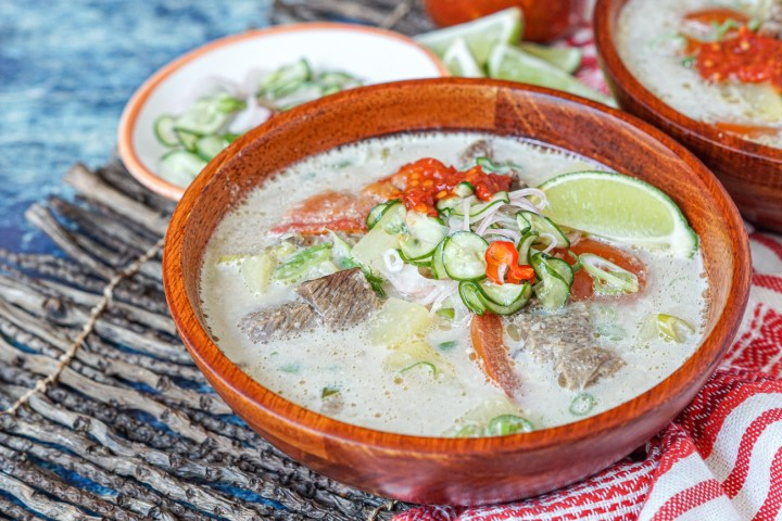 Soto Betawi (Betawi Beef and Coconut Soup) in two wooden bowls topped with a cucumber chilli pickle and Sambal Ulek.